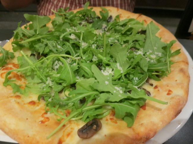Funghi Pizza with mushrooms and fontina. Topped with arugula, truffle oil and shaved Parmesan.