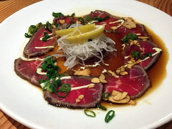 Seared beef sashimi with ponzu, wasabi mayo & garlic chips.
